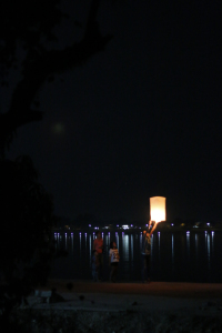 Paper lantern send-off, with the lights of another country across the waters.